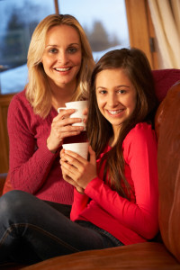 Portrait Of Mother And Daughter Relaxing On Sofa Together With Hot Drink
